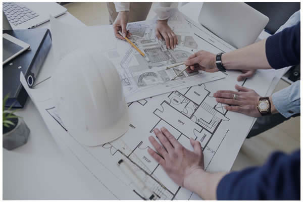 Photo of a construction hard hat on top of blueprints.
