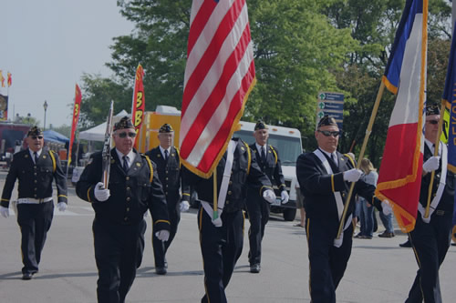 Photo of a veterans day parade. A group of older war veterans are in uniform marching down the street holding flags.