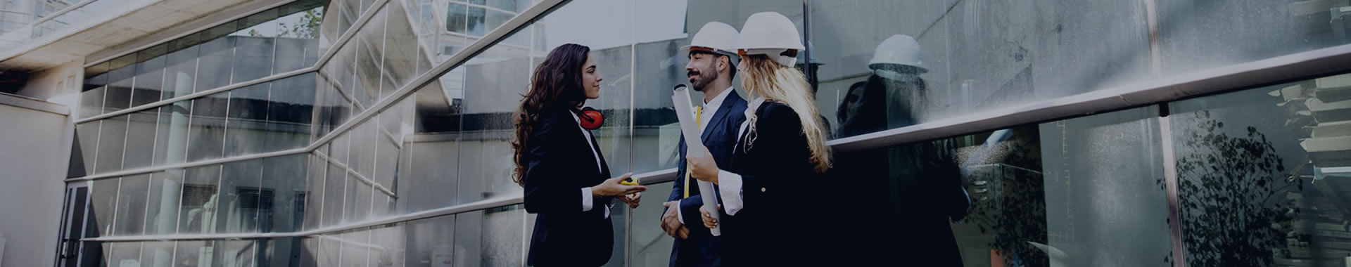A man and woman wearing construction hats talking to a business woman outside of a skyrise that's under construction.
